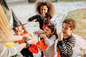 Children in Halloween costumes trick or treating and eating candy.